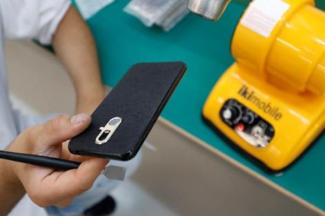 Funcionária mostra telemóvel na fábrica, em Coruche. Foto: REUTERS/Rafael Marchante
