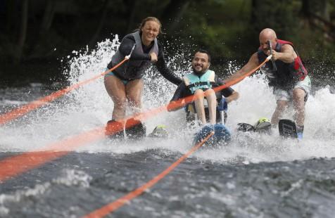 """Christian Budney, no centro, faz ski aquático com Katie Heikkinen e Jim Kovaleski através do programa """"Individual Abilities in Motion and LOF Adaptive Skiers"""", no lago Chapman, nos EUA, a 10 de agosto de 2018. Foto: Jake Danna Stevens/The Times-Tribune via AP"""