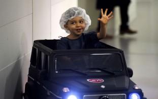 Souhail, com dois anos, acena aos médicos enquanto se dirige para a sala de operações, em França, a 2 de fevereiro de 2018. O hospital tem três carros para reduzir o stress nas crianças antes das cirurgias. Foto: Francois Lo Presti / AFP / Getty